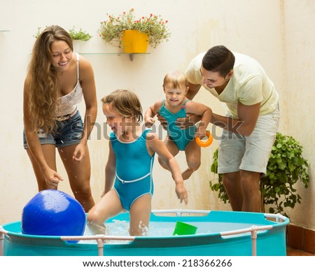 Cheerful couple and little daughters having fun in pool outdoor. Focus on girl  - stock photo