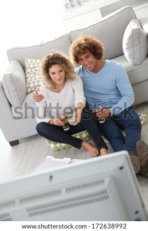 Cheerful couple at home having pizza in font of TV - stock photo