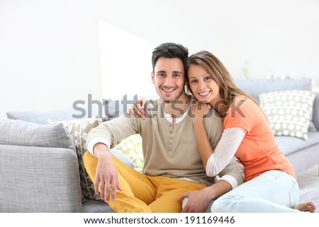 Cheerful couple at home sitting in sofa - stock photo