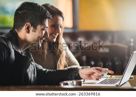 Cheerful couple at the cafe with a laptop, he is pointing at the screen - stock photo