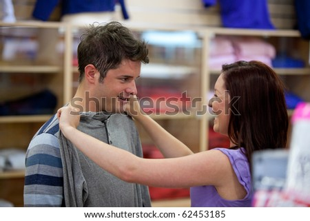 Cheerful couple choosing clothes standing in the men department in a shop - stock photo