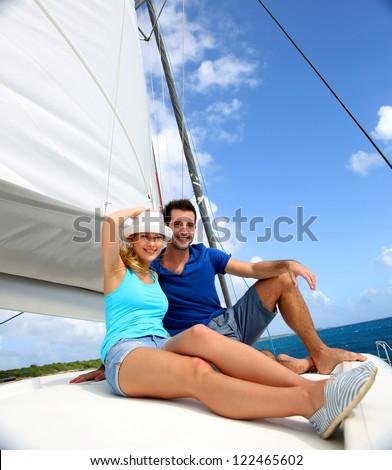 Cheerful couple cruising on a catamaran in Caribbean sea - stock photo