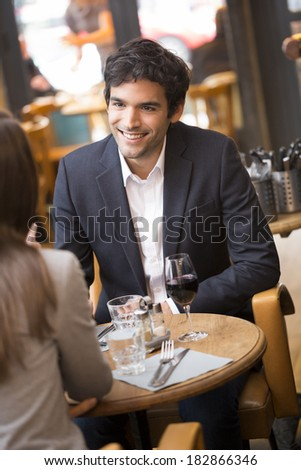 Cheerful couple drinking red wine in French restaurant - stock photo