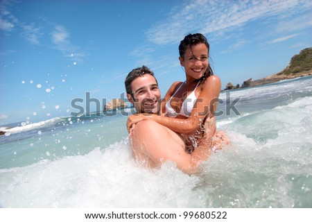 Cheerful couple enjoying the waves