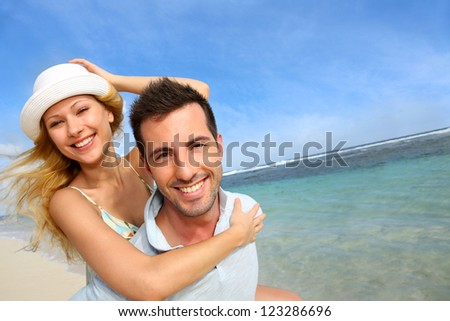 Cheerful couple enjoying vacation at the beach - stock photo