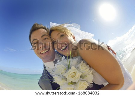 Cheerful couple getting married on the beach - stock photo