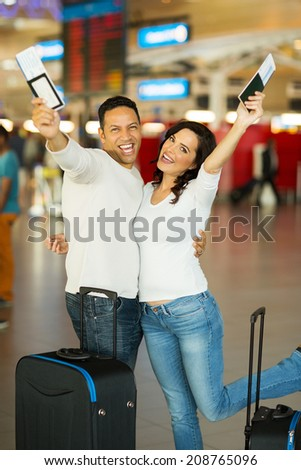 cheerful couple going on a holiday by air - stock photo
