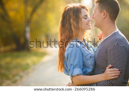 Cheerful couple having fun on summer vacation. Portrait of a happy couple laughing at camera. Young couple in the countryside in autumn. - stock photo