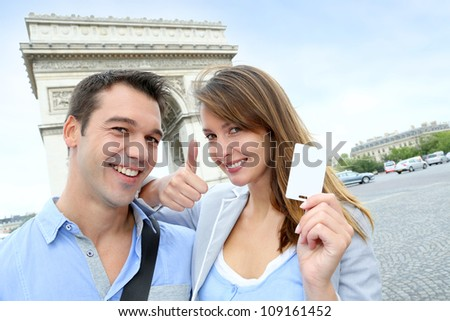 Cheerful couple holding tourist ticket by the Arch of Triumph - stock photo