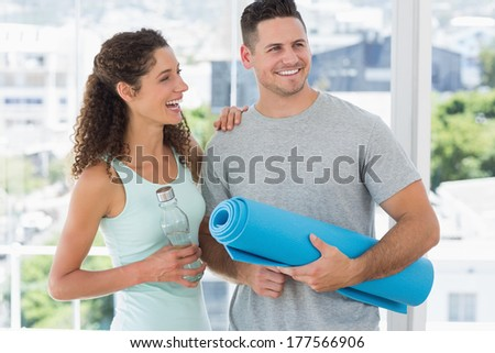 Cheerful couple holding water bottle and exercise mat in exercise room - stock photo
