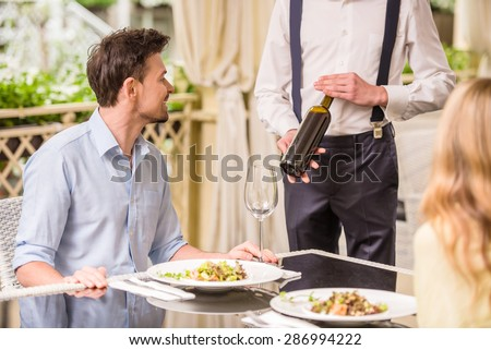 Cheerful couple in a restaurant ordering wine. Romantic dinner. - stock photo