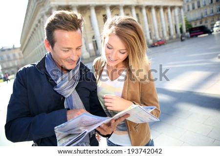Cheerful couple in Bordeaux reading city map - stock photo