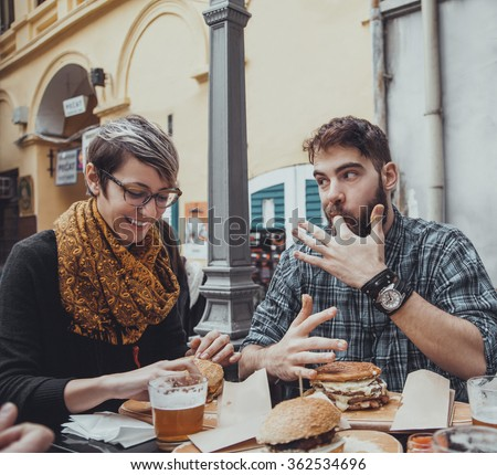 Cheerful Couple In Fast Food Restaurant Eating Burgers - stock photo
