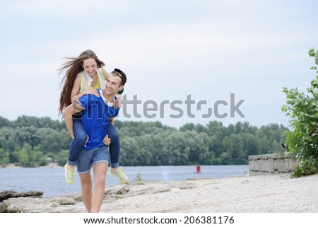 Cheerful couple in love. Girl guy jumped on his back and they run on the beach - stock photo