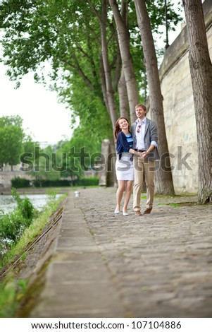 Cheerful couple is dancing on the Seine embankment in Paris - stock photo