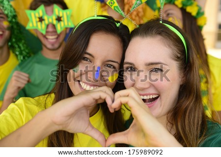 Cheerful couple of Australian or Brazilian or Cameroonian girlfriends soccer fans.   - stock photo