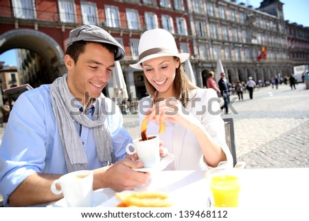 Cheerful couple of tourists eating churros in Madrid - stock photo