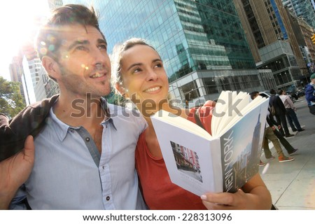 Cheerful couple of tourists visiting New York City - stock photo