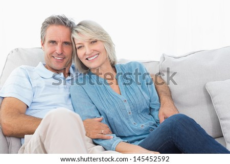 Cheerful couple on their couch smiling at camera at home - stock photo