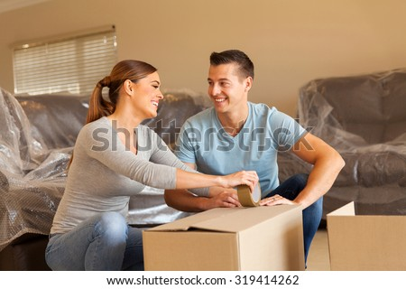 cheerful couple packing for new house - stock photo