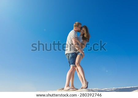 cheerful couple passionate lovers embrace and laughing. Background is beautiful blue sky with glare from the bright midday sun - stock photo