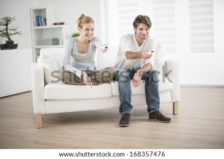 cheerful couple play to video game on a couch - stock photo