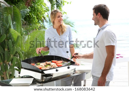 Cheerful couple preparing grilled food on barbecue - stock photo