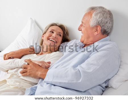 Cheerful couple relaxing on bed at home - stock photo