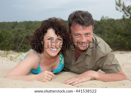 Cheerful couple relaxing together in the sand at beach