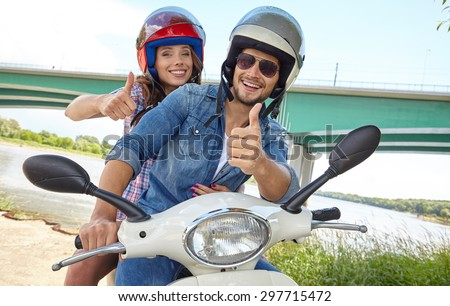 Cheerful couple riding vintage scooter - stock photo