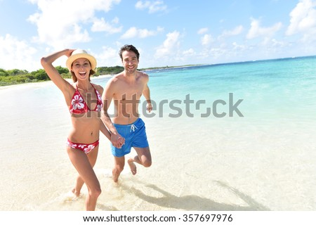 Cheerful couple running on a white sandy beach - stock photo