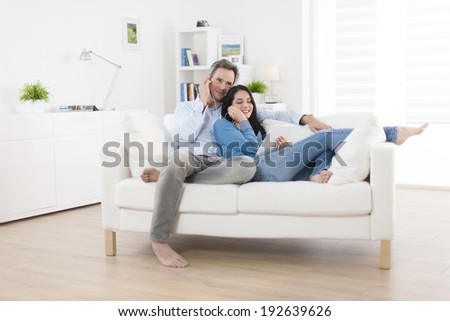 cheerful couple sharing music on digital tablet in sofa at home - stock photo