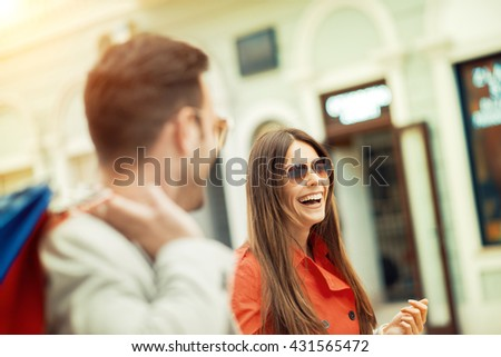 Cheerful couple shopping together in the city.Couple of tourists walking in a city street. - stock photo