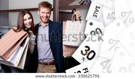 Cheerful couple show their purchases after shopping on sale - stock photo