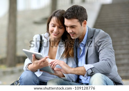 Cheerful couple sitting in stairs with electronic tablet - stock photo