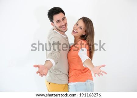 Cheerful couple spreading arms towards camera - stock photo