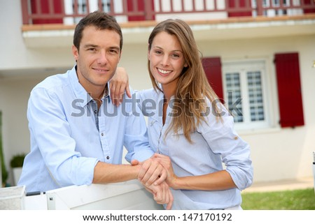 Cheerful couple standing in front of new home - stock photo