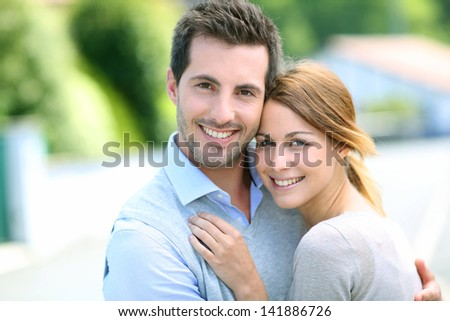 Cheerful couple standing in front of new house - stock photo