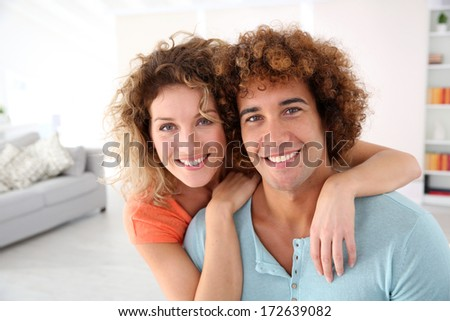 Cheerful couple standing in their new place - stock photo