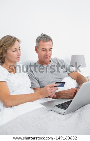 Cheerful couple using their laptop to buy online at home in bedroom - stock photo