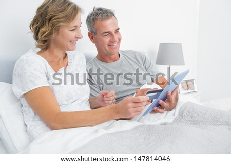 Cheerful couple using their tablet pc to buy online at home in bedroom - stock photo