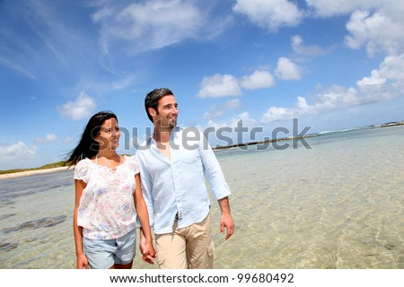 Cheerful couple walking by the sea - stock photo