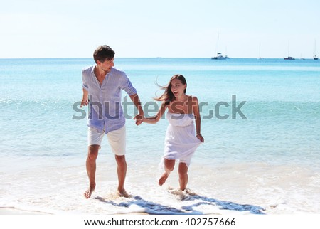 Cheerful couple walking on beach on blue sea background