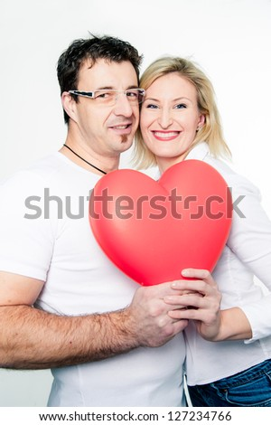 Cheerful Couple with a big red Heart Shape - stock photo