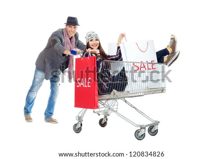 Cheerful couple with a shopping trolley. Isolated over white background. - stock photo