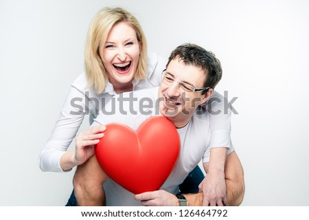 Cheerful couple with big heart in their hands - stock photo