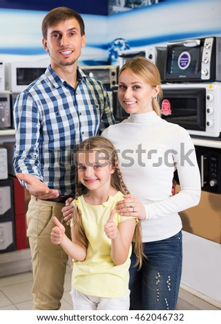 Cheerful couple with girl in store with home electronics