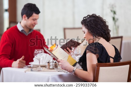 Cheerful couple with menu in a beautiful restaurant making order - stock photo