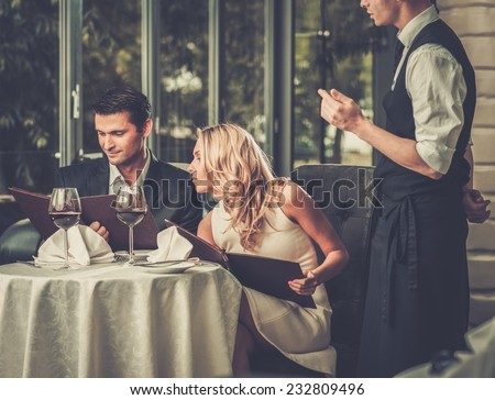 Cheerful couple with menu in a restaurant making order - stock photo