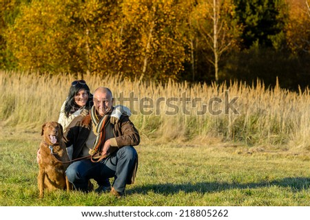 Cheerful couple with retriever dog in autumn countryside sunset - stock photo